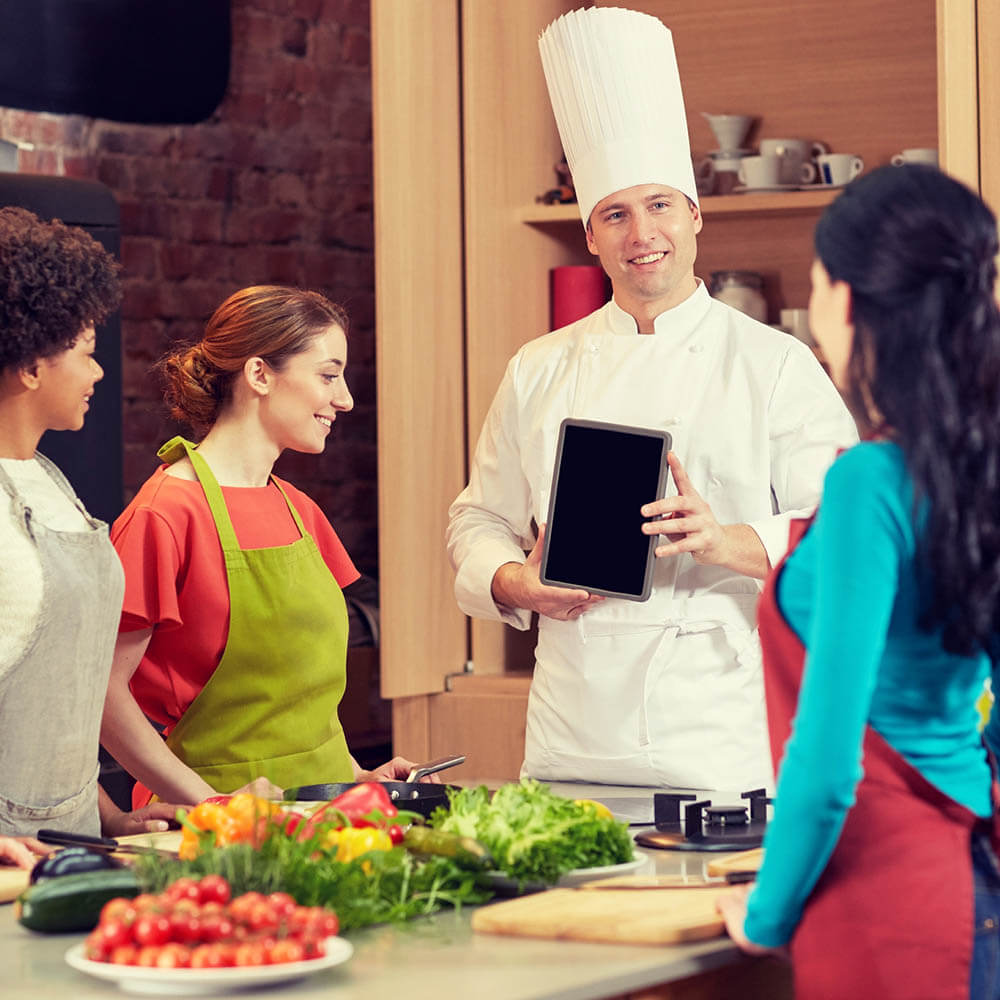 Chef teaching three students in culinary class